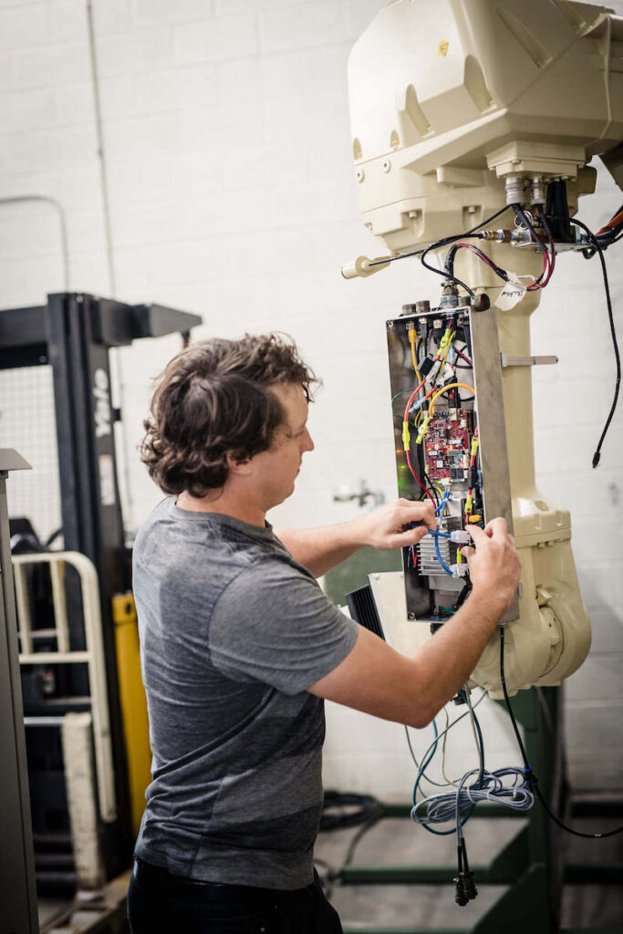 Stratom engineer working on robotic arm