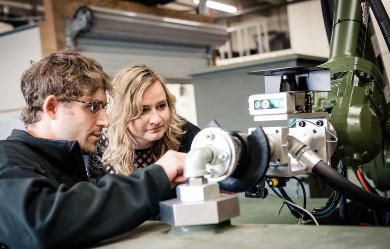 Stratom team working on robotic arm